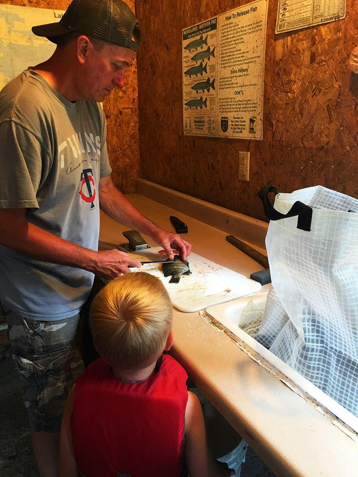 Man cleaning fish with his son at Everett Bay Lodge
