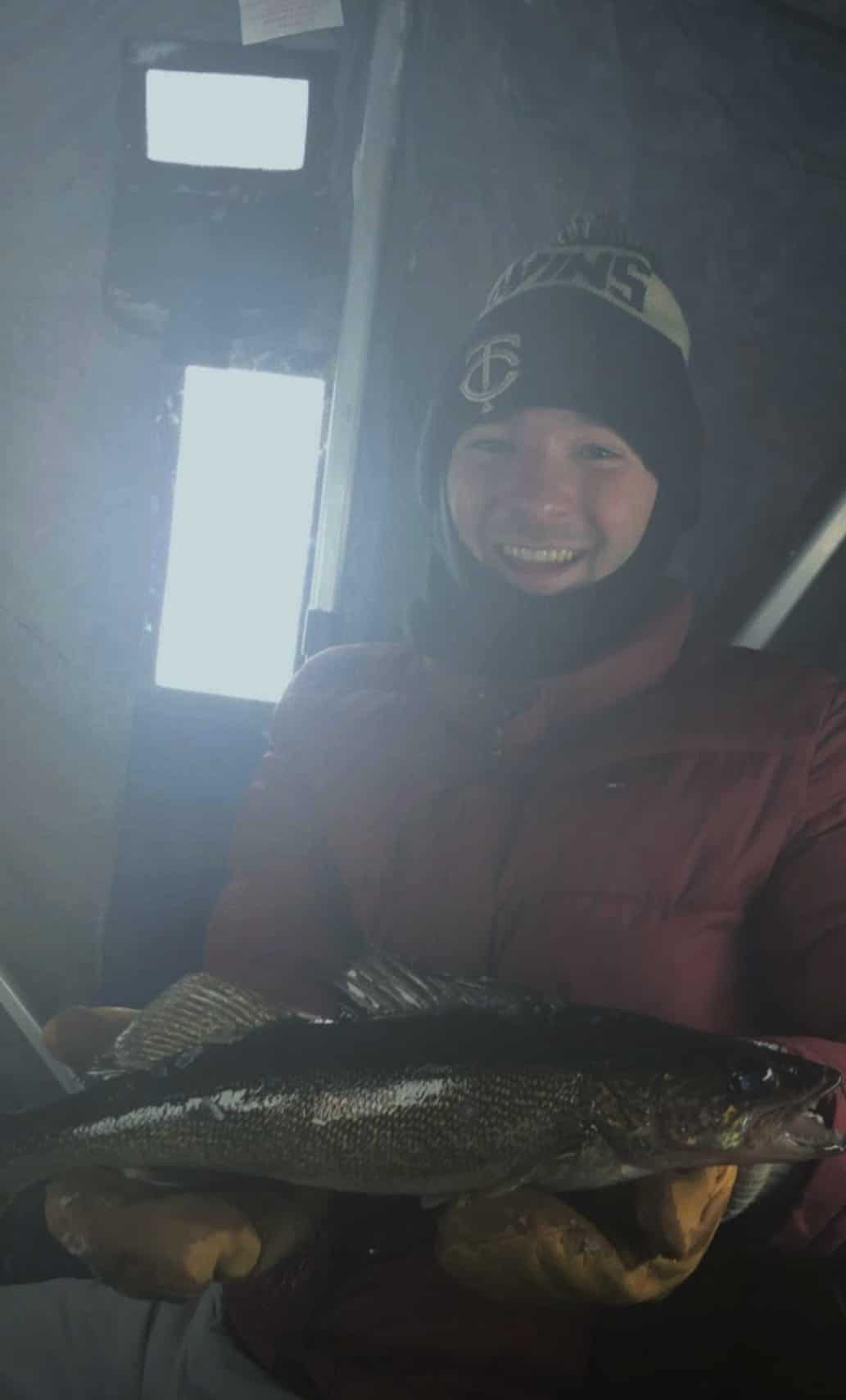 Man in ice house holding walleye